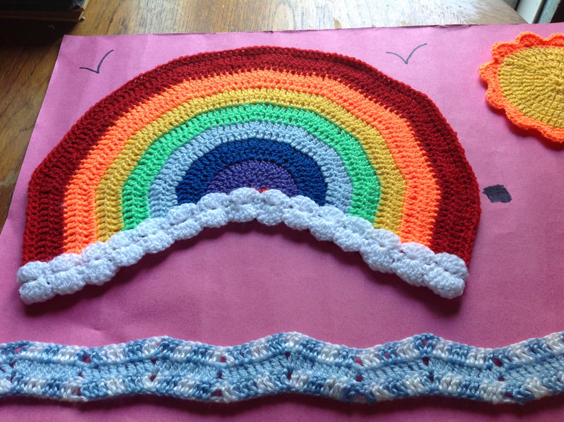 Intricately crocheted rainbow with a sun and the waves of the sea, all crocheted